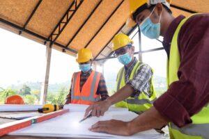 bygningsingeniører som ser på tegninger